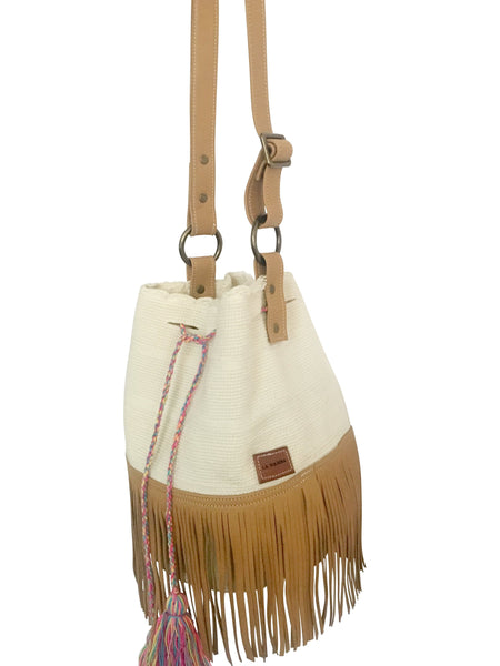 Side image of Wayuu bucket bag purse with brown color leather strap and fringe and tassels; bag is white with colorful tassels