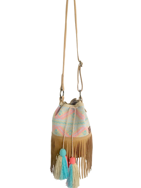 Image of Wayuu bucket bag purse with brown leather strap and fringe and tassels; bag is neutral base with light colored design