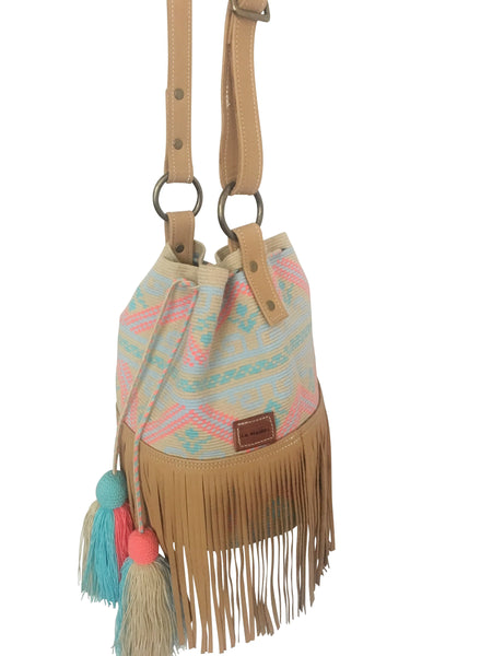 Side image of Wayuu bucket bag purse with brown leather strap and fringe and tassels; bag is neutral base with light colored design