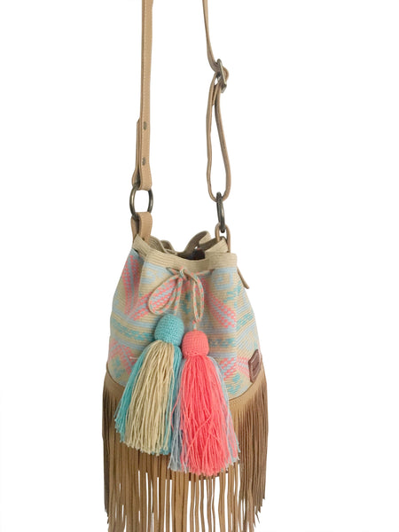 Close up image of Wayuu bucket bag purse with brown leather strap and fringe and tassels; bag is neutral base with light colored design