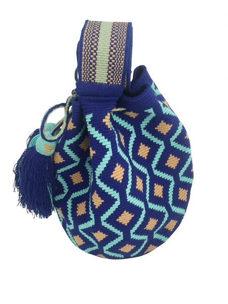 Side angle image of Wayuu mochila purse, drawstring crossbody bag with tassels and cloth strap; royal blue base with light blue and tan design
