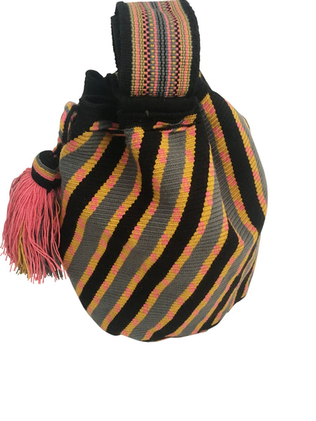Side angle image of Wayuu mochila purse, drawstring crossbody bag with tassels and cloth strap; black base with diagonal design, pink, yellow and grey colors
