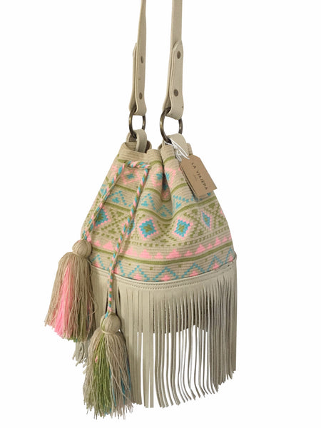 Side angle image of Wayuu bucket bag purse with oatmeal colored leather strap and fringe with tassels; bag is neutral base with pastel color design