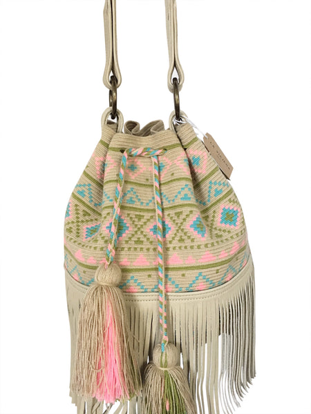 Close up image of Wayuu bucket bag purse with oatmeal colored leather strap and fringe with tassels; bag is neutral base with pastel color design