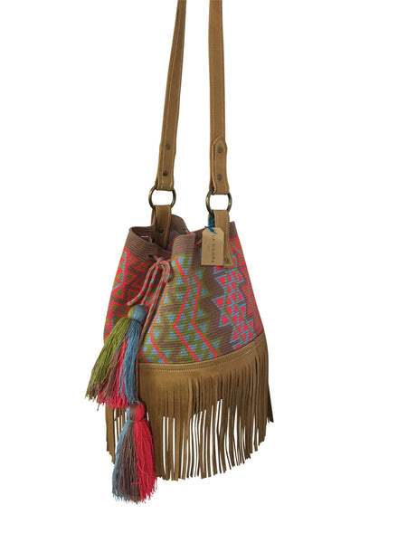 Side angle image of Wayuu bucket bag purse with brown leather strap and fringe and tassels; bag is grey base with bright red, light green and blue design