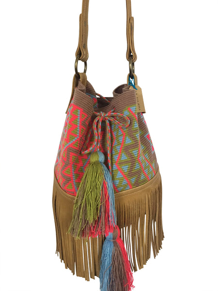 Close up image of Wayuu bucket bag purse with brown leather strap and fringe and tassels; bag is grey base with bright red, light green and blue design