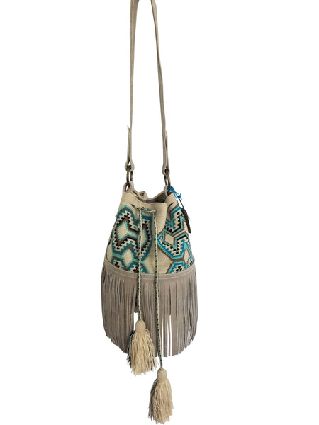 Image of Wayuu bucket bag purse with oatmeal colored leather strap fringe and tassels; bag is neutral base with bright blue, turquoise, grey and black geo design