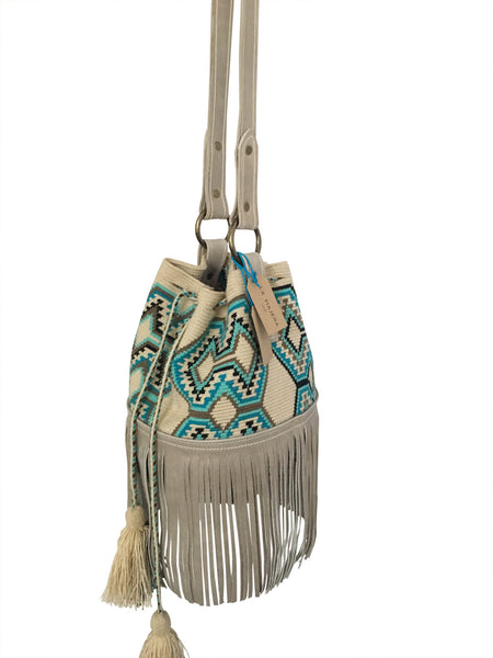 Side angle image of Wayuu bucket bag purse with oatmeal colored leather strap fringe and tassels; bag is neutral base with bright blue, turquoise, grey and black geo design