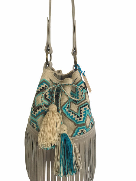 Close up image of Wayuu bucket bag purse with oatmeal colored leather strap fringe and tassels; bag is neutral base with bright blue, turquoise, grey and black geo design