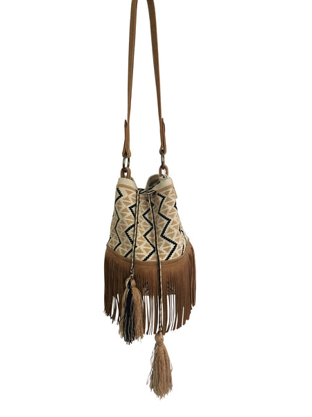 Image of Wayuu bucket bag purse with brown leather strap and fringe and tassels; bag is cream white base with camel brown and black design