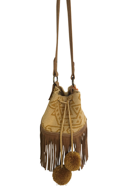 Image of Wayuu bucket bag purse with brown leather strap and fringe and pompoms; bag is tan with mustard yellow design