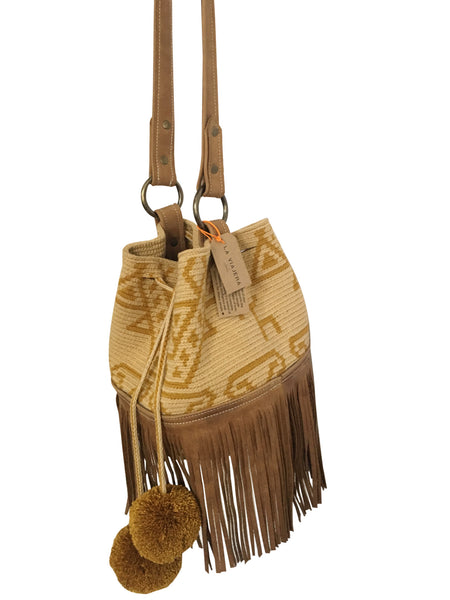 Side angle image of Wayuu bucket bag purse with brown leather strap and fringe and pompoms; bag is tan with mustard yellow design