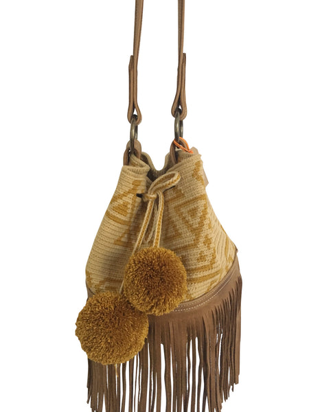 Close up image of Wayuu bucket bag purse with brown leather strap and fringe and pompoms; bag is tan with mustard yellow design