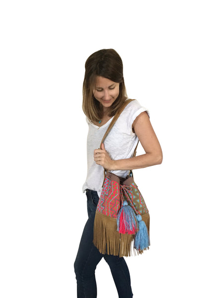 On body image of Wayuu bucket bag purse with brown leather strap and fringe and tassels; bag is grey base with bright red, light green and blue design