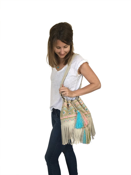 On body image of Wayuu bucket bag purse with oatmeal colored leather strap and fringe with tassels; bag is neutral base with pastel color design