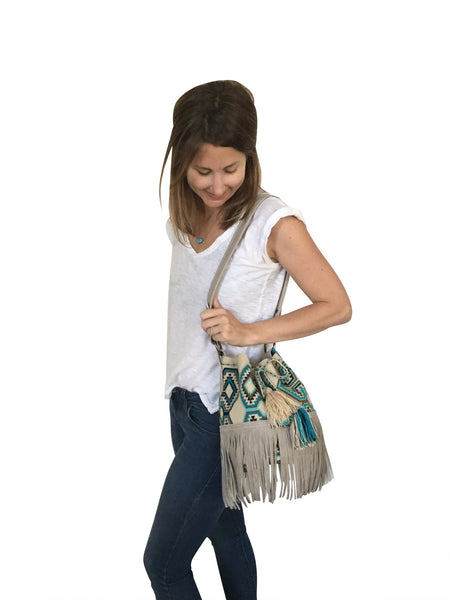 On body image of Wayuu bucket bag purse with oatmeal colored leather strap fringe and tassels; bag is neutral base with bright blue, turquoise, grey and black geo design