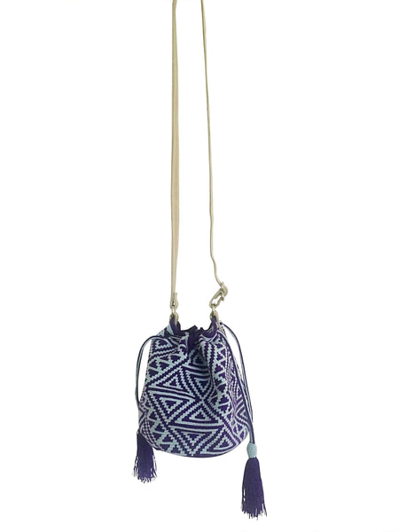 Image of Wayuu mini mochila bucket bag purse with adjustable leather strap, drawstring and two tassels; bag has geometric design equally blue and light blue colored