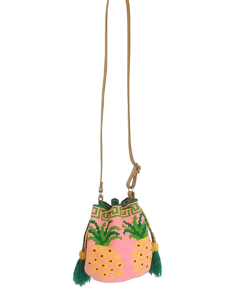 Image of Wayuu mini mochila bucket bag purse with adjustable leather strap, drawstring and two side tassels; bag has pink base with pineapple design