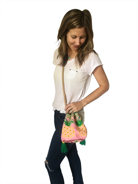 On body image of Wayuu mini mochila bucket bag purse with adjustable leather strap, drawstring and two side tassels; bag has pink base with pineapple design