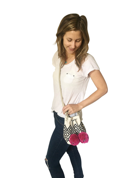 On body image of Wayuu mini mochila bucket bag purse with adjustable leather strap, drawstring and two pompoms; bag has white base with black geometric design