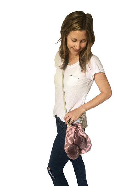 On body image of Wayuu mini mochila bucket bag purse with adjustable leather strap, drawstring and two pompoms; bag has pink base with purple grey design