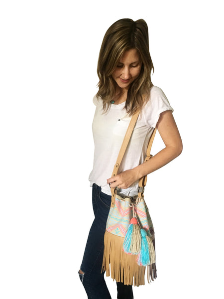 On body image of Wayuu bucket bag purse with brown leather strap and fringe and tassels; bag is neutral base with light colored design