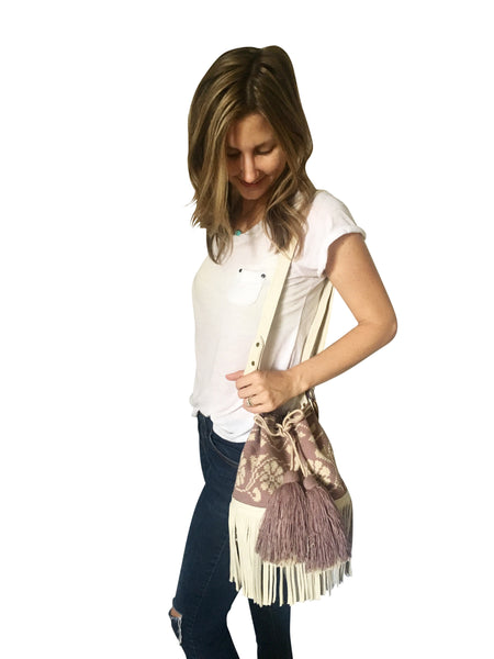 On body image of Wayuu bucket bag purse with oatmeal color leather strap and fringe and tassels; bag is light purple with cream flower desing