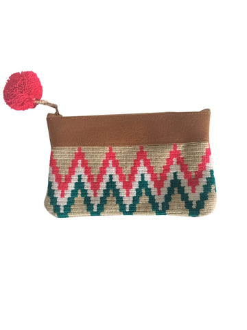 Image of handmade Wayuu zipper pouch with woven textile in colorful zigzag pattern; pouch has colorful pompom and leather at the top