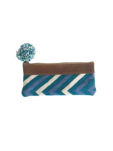Image of handmade Wayuu zipper pouch with woven textile in a blue, teal and white linear design; pouch has colorful pompom and brown leather at the top