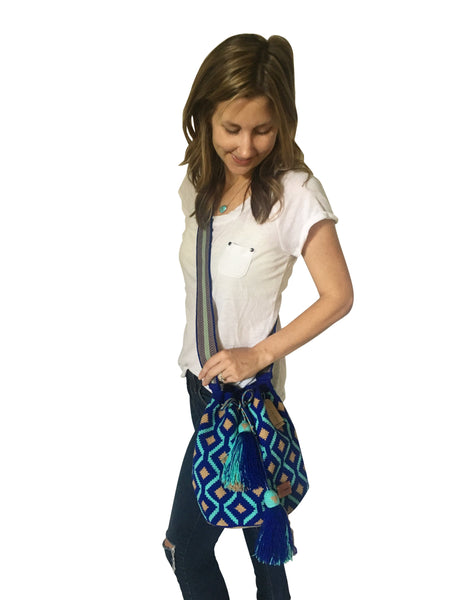 On body image of Wayuu mochila purse, drawstring crossbody bag with tassels and cloth strap; royal blue base with light blue and tan design