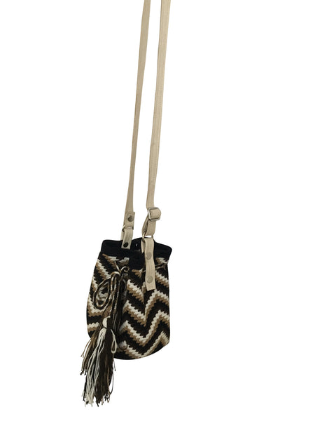 Side angle image of Wayuu mini mochila bucket bag purse with adjustable oatmeal colored leather strap, drawstring and two tassels; bag is dark brown, black, neutral zig zag design