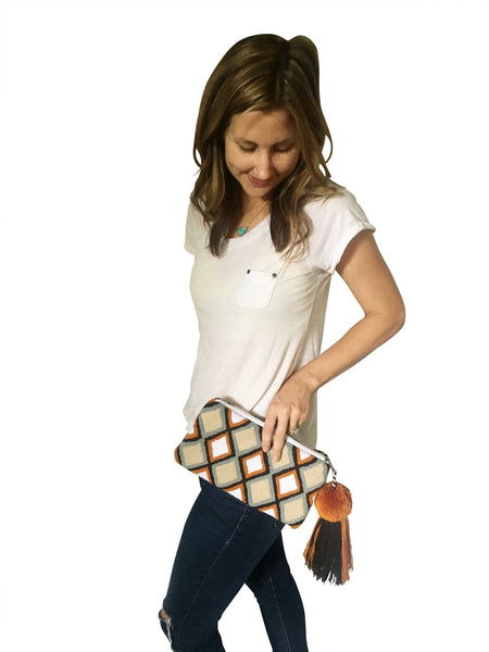On body image of Wayuu small clutch purse with pom pom tassel and zipper; rectangular shaped with tan base color and diamond design with orange, grey and black colors