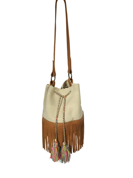 Image of Wayuu bucket bag purse with brown leather strap and fringe and tassels; bag is white with colorful tassels