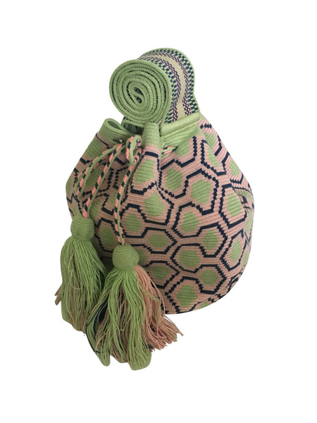 Side angle image of una hebra Wayuu mochila purse, drawstring crossbody bag with tassels - base color light green with navy and light pink sextagon design