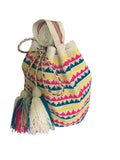 Side angle image of una hebra Wayuu mochila purse, drawstring crossbody bag with tassels - base color white with yellow, blue and bright pink small wave design