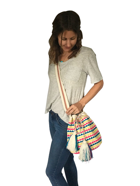 On body image of una hebra Wayuu mochila purse, drawstring crossbody bag with tassels - base color white with yellow, blue and bright pink small wave design