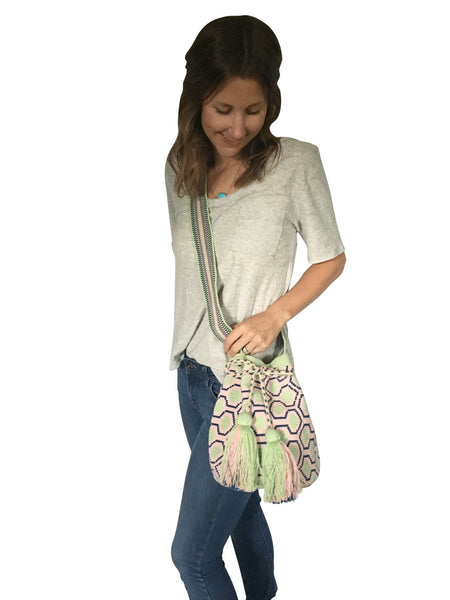 On body image of una hebra Wayuu mochila purse, drawstring crossbody bag with tassels - base color light green with navy and light pink sextagon design