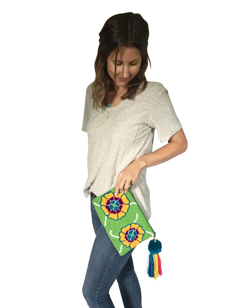 On body image of Wayuu tapizado small clutch purse with pom pom tassel; rectangular shape with bright green base and two colorful flowers on each side