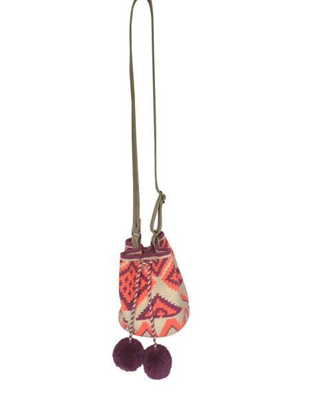Image of Wayuu mini mochila bucket bag purse with adjustable gray colored leather strap, drawstring and two pompoms; bag is a white base color with geo patterns in coral and purple