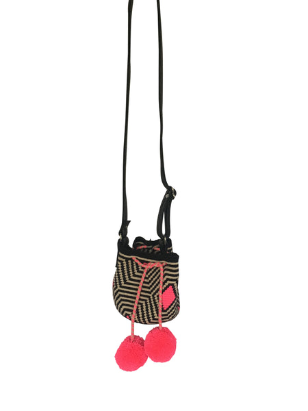 Image of Wayuu mini mochila bucket bag purse with adjustable black leather strap, drawstring and two pompoms; bag is a black and white striped with hot pink detal