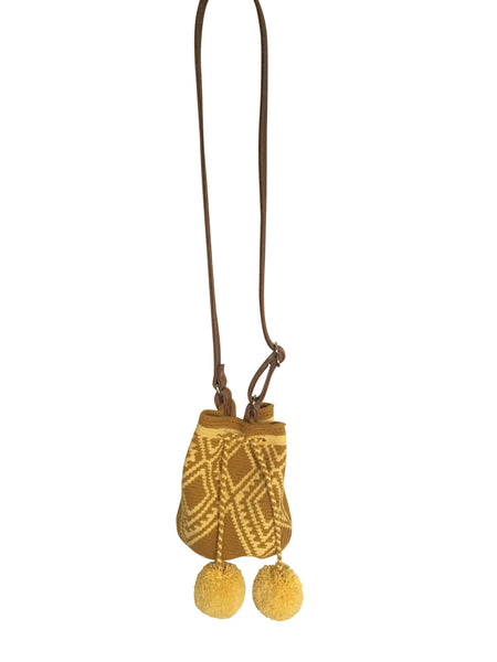 Image of Wayuu mini mochila bucket bag purse with adjustable brown leather strap, drawstring and two pompoms; bag mustard yellow base with light yellow design