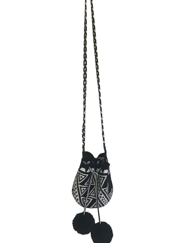 Image of Wayuu mini mochila bucket bag purse with black and white, braided cloth strap, drawstring and two black pompoms; bag is a black base with white geo design