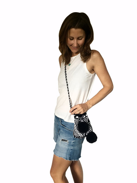 On body image of Wayuu mini mochila bucket bag purse with black and white, braided cloth strap, drawstring and two black pompoms; bag is a black base with white geo design