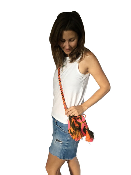 On body image of Wayuu mini mochila bucket bag purse with colorful, braided cloth strap, drawstring and two tassels; bag dark brown base with bright pink and orange design