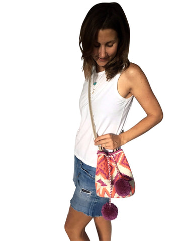 On body image of Wayuu mini mochila bucket bag purse with adjustable gray colored leather strap, drawstring and two pompoms; bag is a white base color with geo patterns in coral and purple