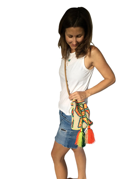 On body image of Wayuu mini mochila bucket bag purse with adjustable brown leather strap, drawstring and two tassels; bag is neutral base dark green, bright orange and bright yellow design