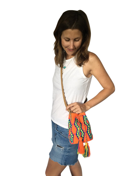 On body image of Wayuu mini mochila bucket bag purse with adjustable light brown leather strap, drawstring and two tassels; bag is bright orange base with bright blue, yellow and green geo design
