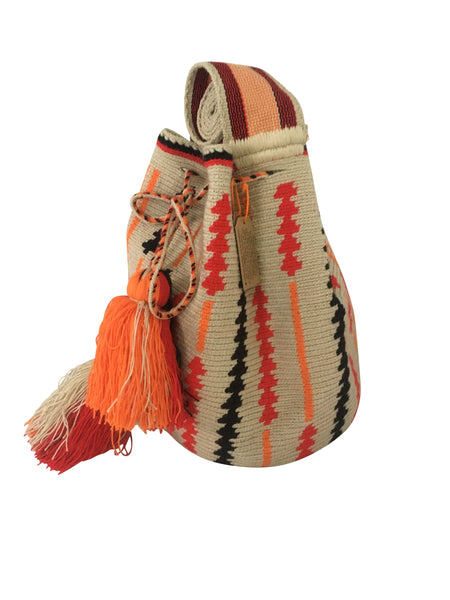 Side angle image of two strand Wayuu mochila purse, drawstring crossbody bag with tassels - base color light tan with black, orange and red arrow shaped design