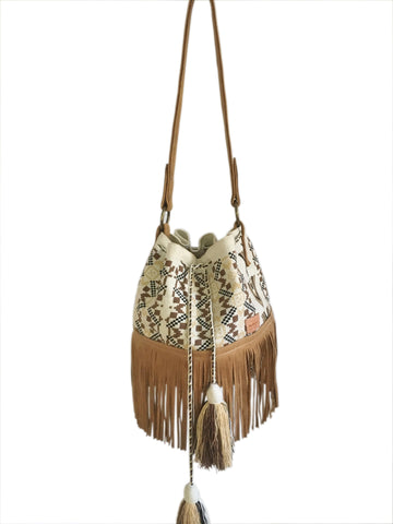 Image of Wayuu bucket bag purse with brown leather strap and fringe and tassels; bag is white base with brown, dark brown and tan design