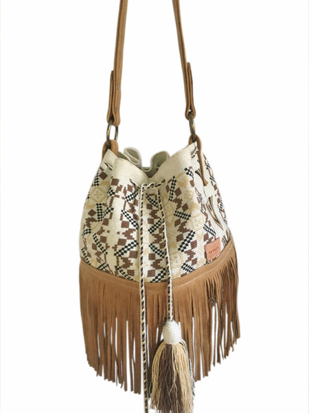 Close up image of Wayuu bucket bag purse with brown leather strap and fringe and tassels; bag is white base with brown, dark brown and tan design